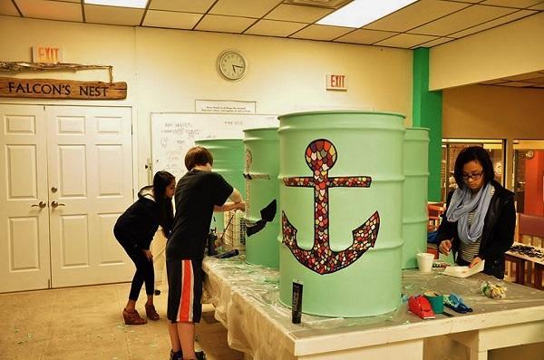 Teen artists work on trash barrels for Stage Fort Park at the Teen Artist Guild.
