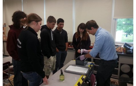 Science teacher Mr. John Barry demonstrates new equipment to his students.