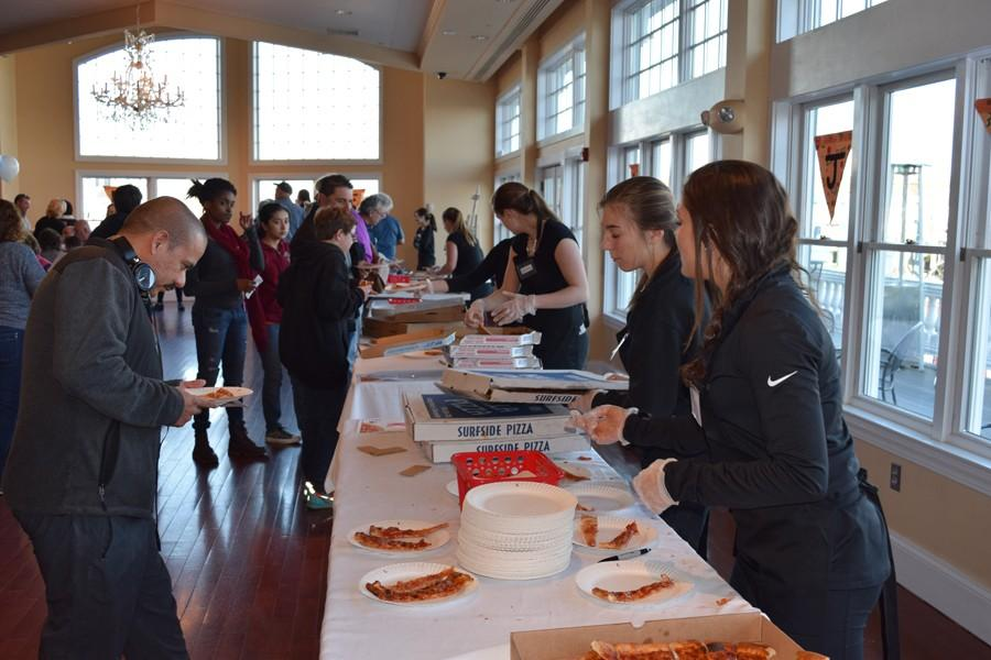 Leanna Hendershott and Julianna Costanzo (right) serve pizza at the Interact annual pizza taste-off.