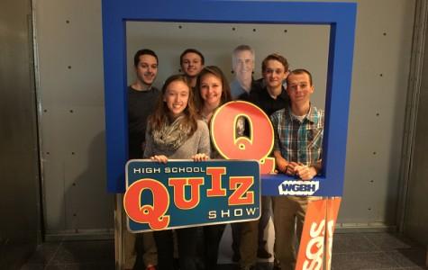 (From left) Tom Vaiarella, Hannah Zuidema, Mike Vaiarella, Matilda Grow, Noah Stevens, and Reilly Zubricki pose with cut out of Billy Costa, host of High School Quiz Show