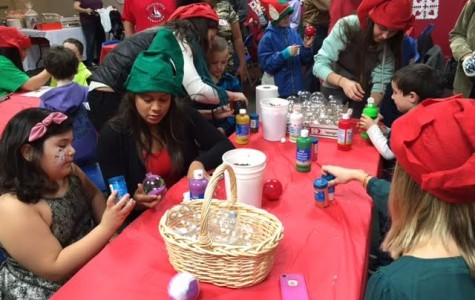 Miranda D'Oleo helps a party goer decorate a Christmas ornament at the annual Interact Pathways Christmas party