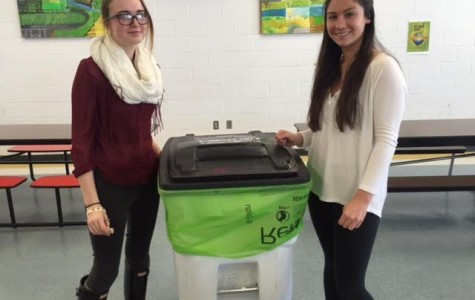 E-club members Gwen Koehne and Lauren Benchoff set up composting bins in the cafeteria