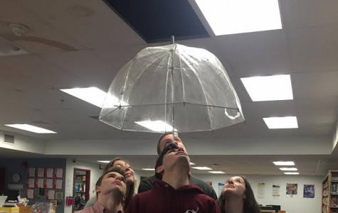 Students pose with umbrella under  the latest leak in the library