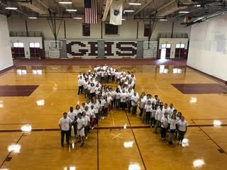 Students and staff pose for a group photo to show their support for breast cancer research