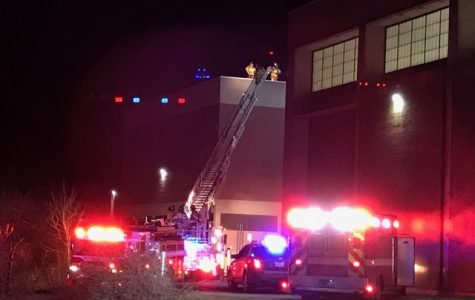 Fire officials stand on the roof of O'Maley Innovation Middle School after flames began coming out of a vent.