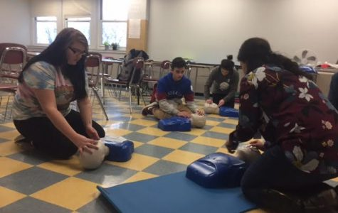 Ms. Francis (right) demonstrates proper CPR procedures to her students