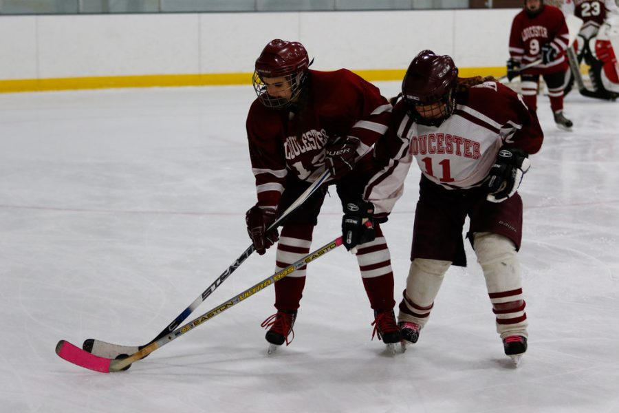 Senior+Sophia+Pata+battles+for+the+puck+against+head+coach+Brittnay+Devlin+in+Sunday%27s+alumni+game