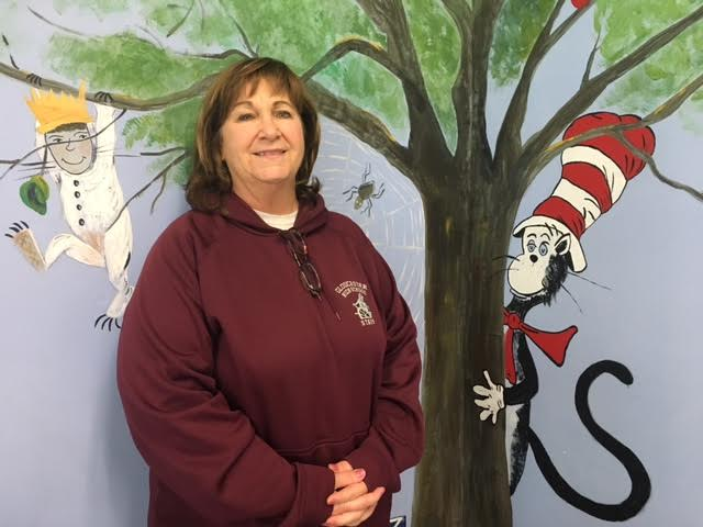 Mrs. Papows poses by the Dr. Seuss mural she and her sister painted on her classroom wall.