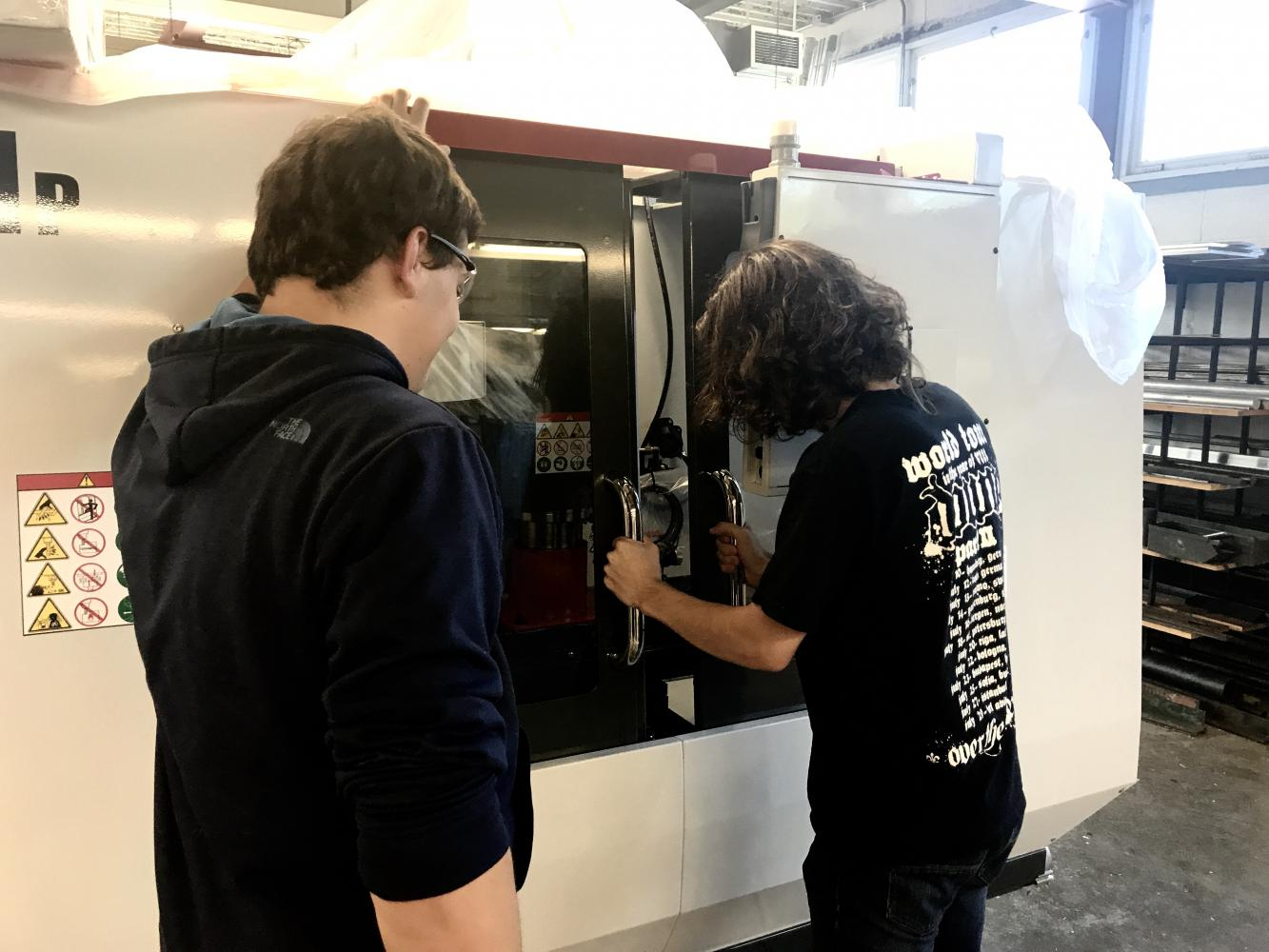 Vocational students huddle around new equipment.