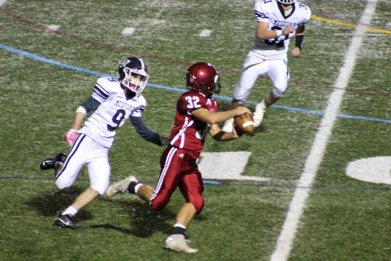 Marc Smith (32) attempts to throw as he is being rushed by a Medford player