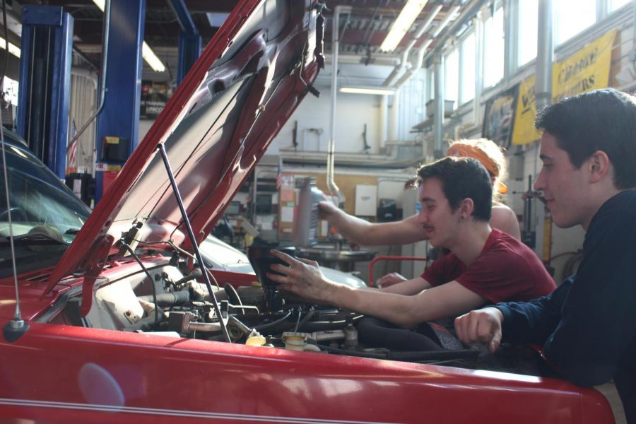 Senior Dominic Romeo (center) works on an engine with other auto students