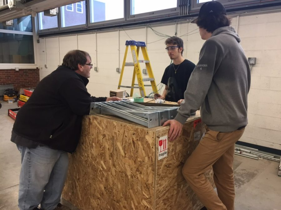 Electrical teacher Robert Devlin (left) works with Dylan Piscitello and Nico Taormina