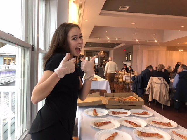 Interact member Rachel Vincent serves pizza at the 11th Annual Pizza Taste-Off on April 4th