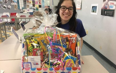 DECA member Sam Gross holds one of the baskets up for grabs in their annual spring raffle