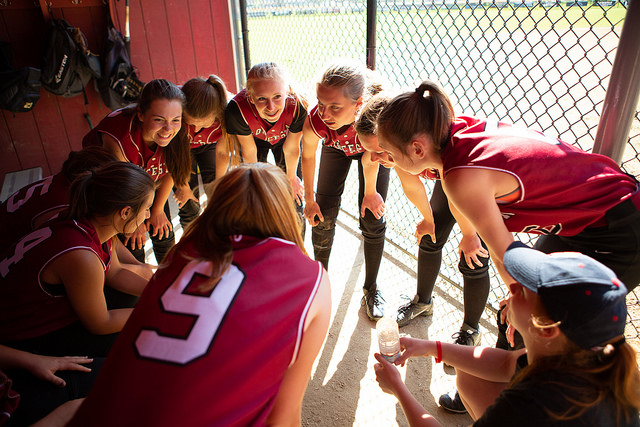 Softball+team+huddles+in+preparation+for+their+game+