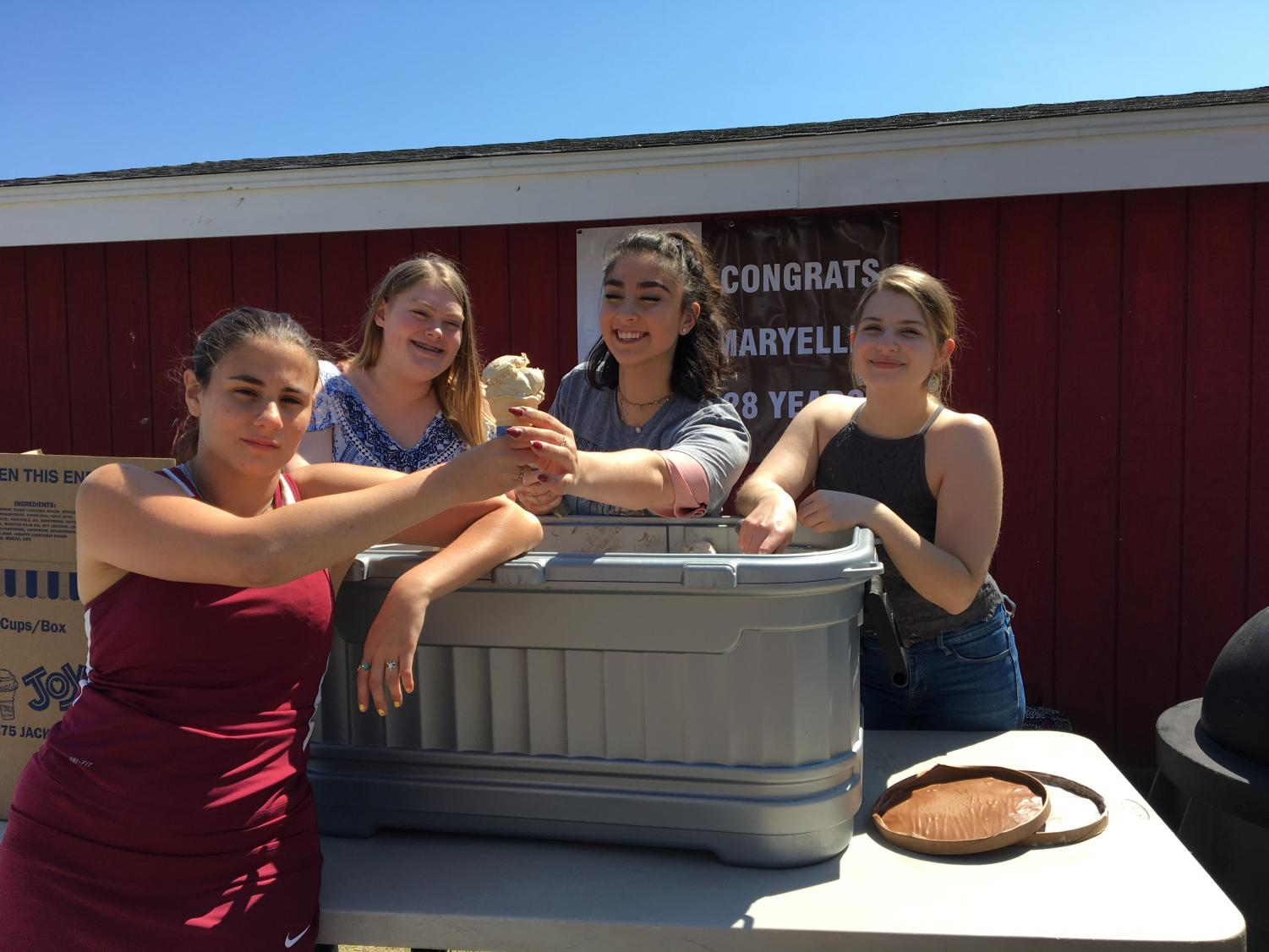 (from left) Allie Sears, Delaney Benchoff, and Rachel Belanger serve junior Tori Carini ice cream at Zielksi's retirement party