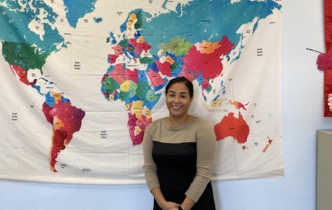 GHS' new Spanish teacher, Señorita Robles, poses by the map in her new classroom