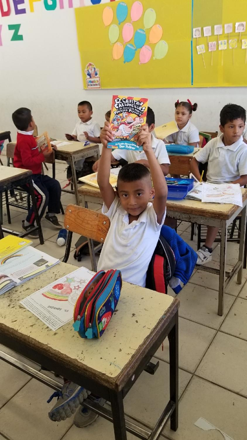 An elementary school boy in Puerto Vallarta expresses his joy after receiving his new book.