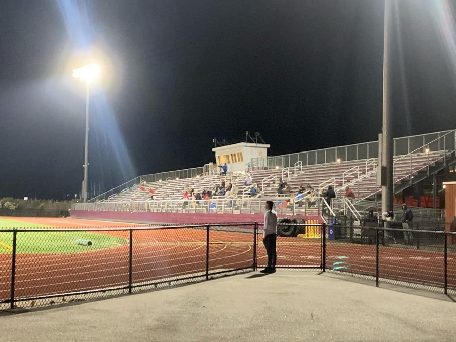 An onlooker watches a sparsely attended field hockey game