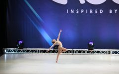 Caitlyn Muniz leaps across the stage at a competition