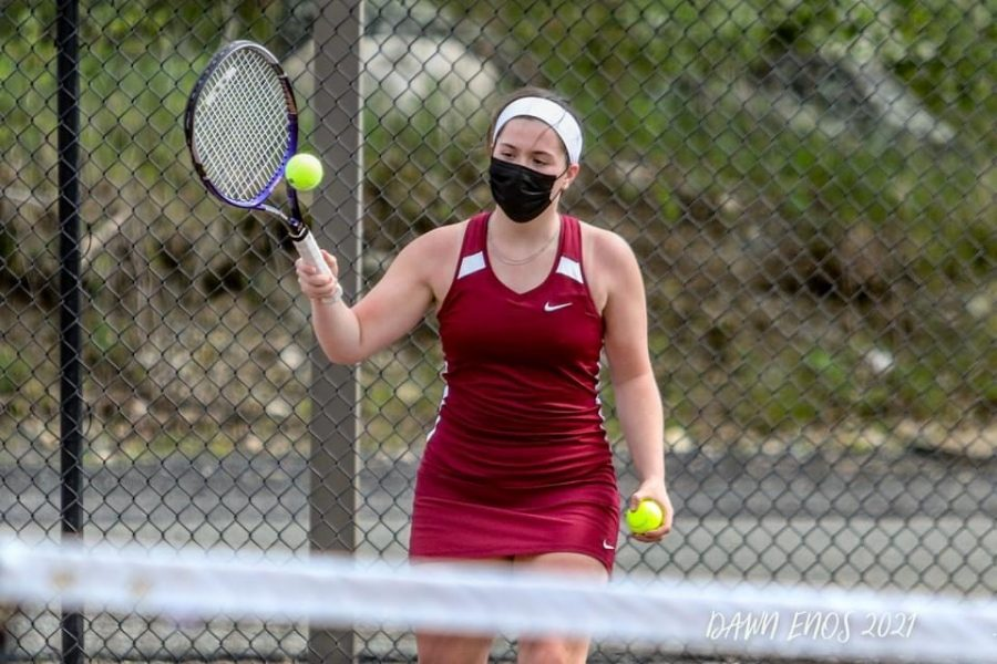 Junior Marina Sullivan rallies in her doubles match, securing a win.